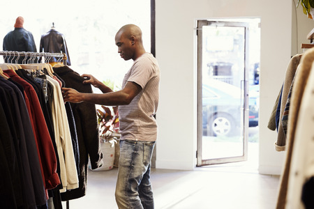 Jonge zwarte man bladeren door kleding op een spoor in een winkel Stockfoto