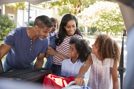 休暇のために出発する家族は車に荷物を積み込む 写真素材