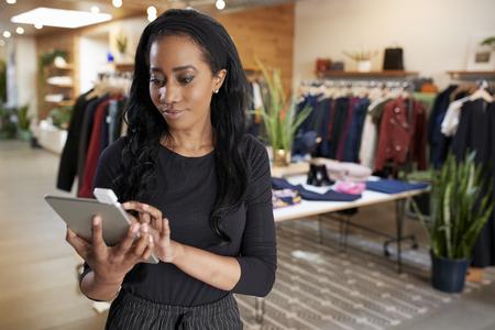 衣料品店でタブレットコンピュータを使用して若い黒人女性