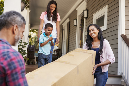 Family Carrying Big Box Purchase Into House Stockfoto
