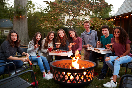 Teenagers at a fire pit with take-away pizzas look to camera