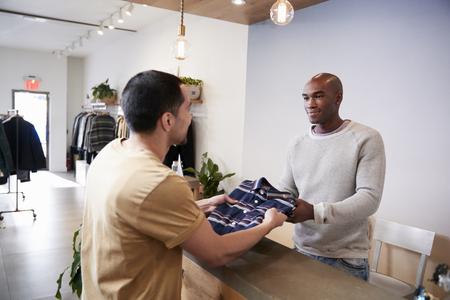 衣料品店のカウンターで客にサービスを提供する男