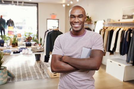 Young black man smiling to camera in a clothes shop Stock Photo