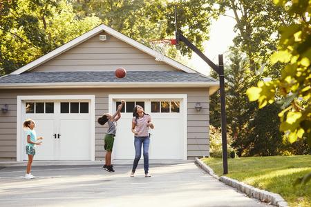Moeder en kinderen spelen basketbal op oprit thuis