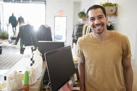 Assistente maschio che sorride dietro il contatore in un negozio di vestiti Archivio Fotografico - 93403069