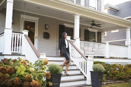 Businesswoman Leaving Suburban House For Commute To Work