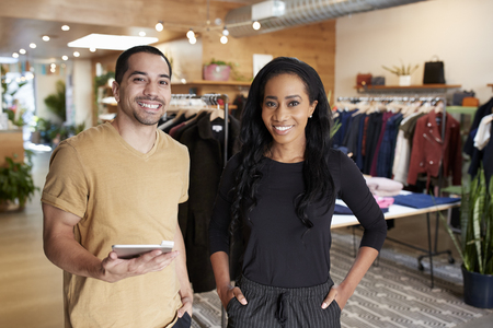 Young couple with tablet smiling to camera in a clothes shop Stock Photo
