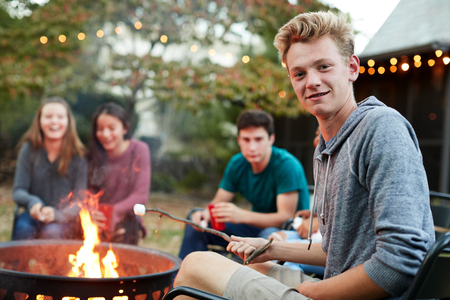 Teenage boy with friends toasting marshmallow at a fire pit