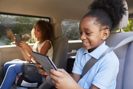 車の旅でデジタルデバイスを使用する子供たち
