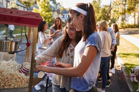 女の子は近所のブロックパーティーで自分自身にポップコーンを提供します