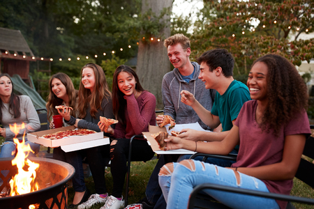 Teenagers at a fire pit eating take-away pizzas, close up