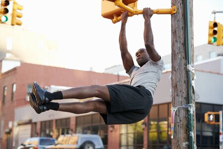 Young black man doing pull ups from crossing light in street