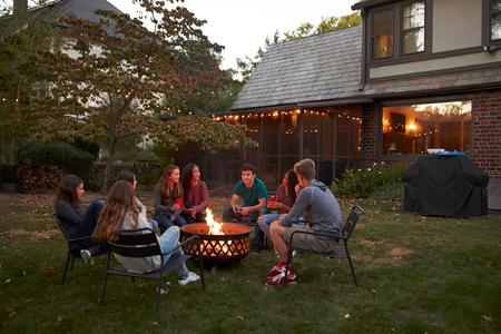 Teenagers sit talking around a fire pit in a garden at dusk Standard-Bild