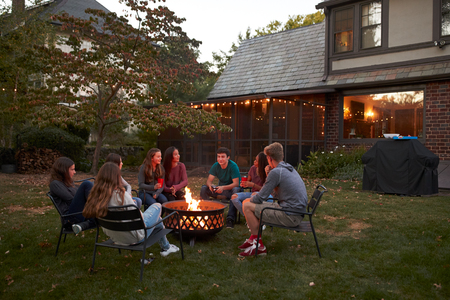 Teenagers sit talking around a fire pit in a garden at dusk Stockfoto