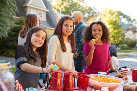 Pre-teen girls smiling to camera at a block party, close up Stock Photo