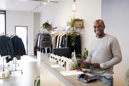 Mężczyzna asystent uśmiechający się za ladą w sklepie odzieżowym