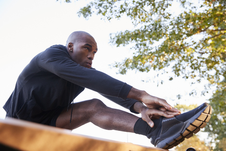 Young black man stretching leg on a bench in park, close up Stock Photo