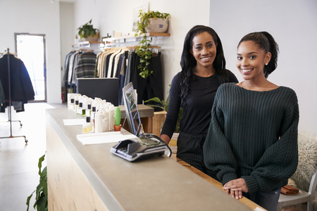 Two women smiling behind the counter in clothing store Imagens