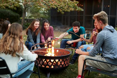 십대 친구 마쉬 멜 로우 토스트 화재 구 덩이 라운드 앉아 스톡 콘텐츠