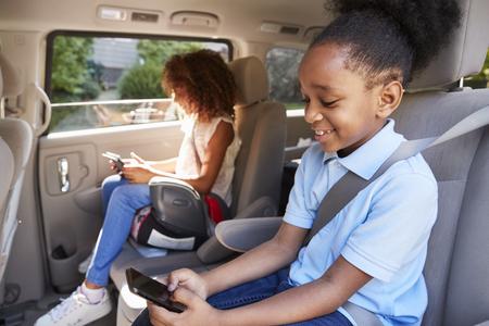Kinderen met behulp van digitale apparaten op auto reis Stockfoto