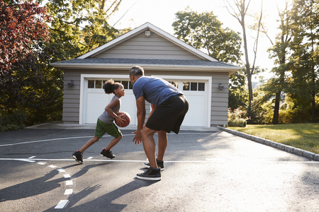 Father And Son Playing Basketball On Driveway At Home