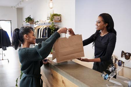 Kobieta obsługująca klienta przy kasie w sklepie odzieżowym Zdjęcie Seryjne