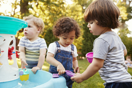 Group Of Young Children Playing With Water Table In Garden 스톡 콘텐츠