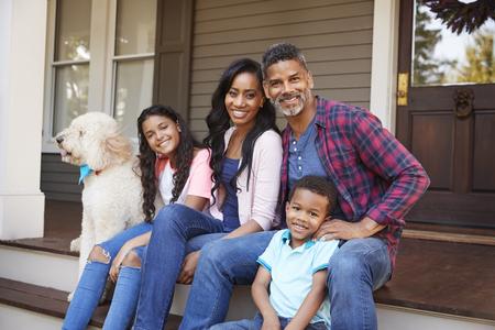 Gezin met kinderen en hond zitten op trappen van thuis
