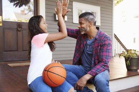 Father And Daughter Discussing Basketball On Porch Of Home Stok Fotoğraf