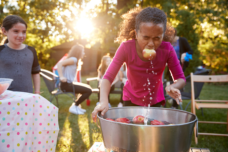 Pre-teen meisje, appel in de mond, appel dobberen op tuinfeest