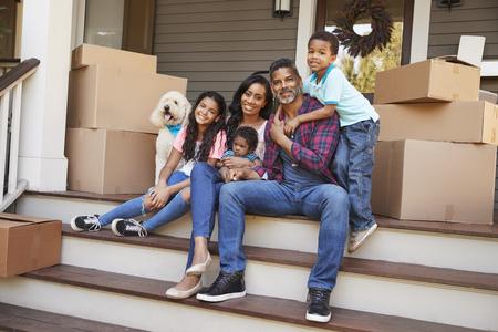 Gezin met kinderen en hond buiten huis op verhuisdag Stockfoto