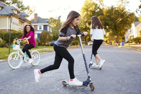 スクーターと自転車で通りで遊ぶ女の子、クローズアップ 写真素材