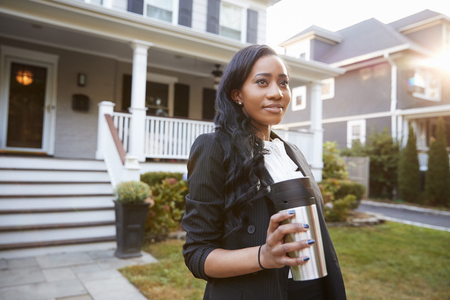 Businesswoman With Cup Of Coffee Leaving Suburban House For Work Stock fotó
