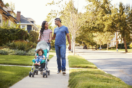 Couple Push Daughter In Stroller As They Walk Along Street Stock Photo