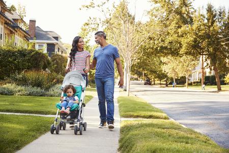 Para pchać córkę w wózku, gdy idą wzdłuż ulicy