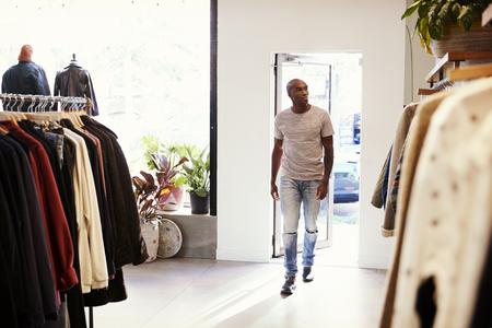 Jonge zwarte man lopen in een kledingwinkel