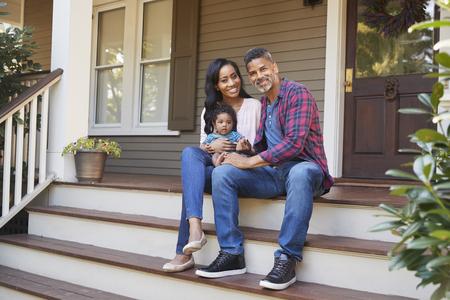 famille avec bébé fils assis sur les marches menant au porche de la maison