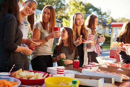 女の子はブロックパーティーの食べ物テーブルで話して立って、クローズアップ 写真素材