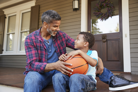 Father And Son Discussing Basketball On Porch Of Home Stock Photo