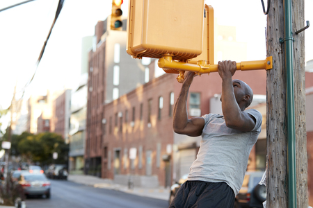 Young black man doing chin ups from crossing light in street Stock Photo - 93402435