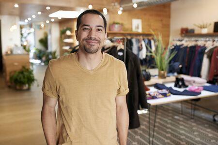 衣料品店に立つ若いヒスパニック系の男の笑顔