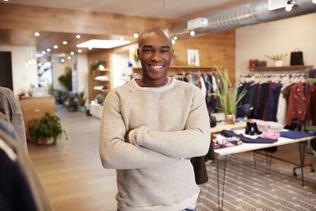 Young black man smiling to camera in a clothes shop Banco de Imagens
