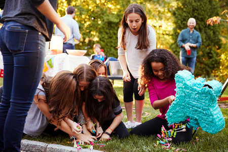 Young girls collecting sweets from a broken pi–ata