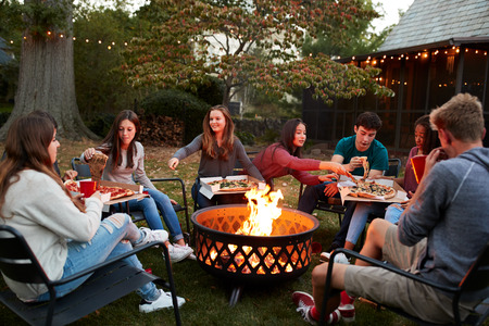 Teenage friends sit round a fire pit eating take-away pizzas