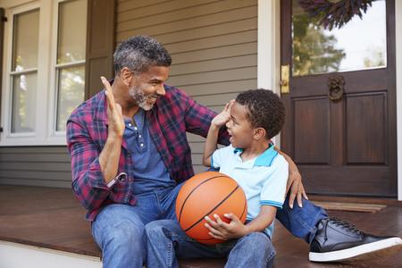 父と息子が自宅のポーチでバスケットボールについて話し合う 写真素材