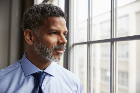Middle aged black businessman looking out of window