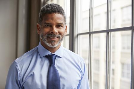 Midden oude zwarte zakenman die aan camera glimlacht