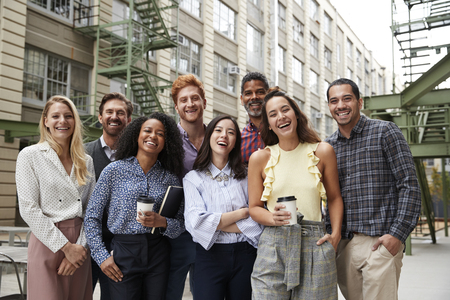 Friendly coworkers laugh to camera outside their workplace Foto de archivo