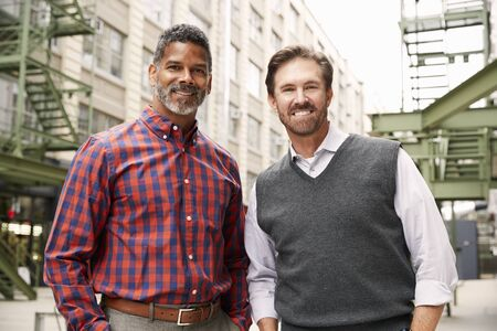 Two middle aged make colleagues outside their workplace Stock Photo