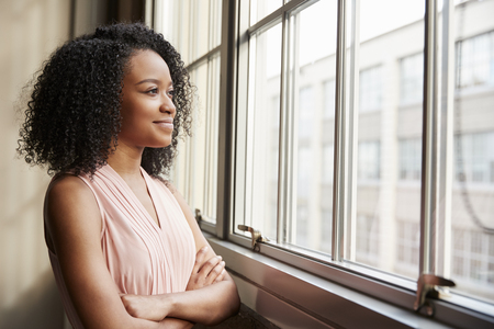 Young black woman with arms crossed looking out of window Banco de Imagens